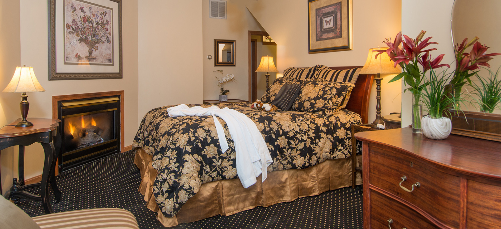 Chaise, table with lamp, fireplace with picture above, queen sleigh bed with gold & black bedding, chest with mirror above