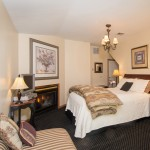 Franconia Falls Room with chaise, fireplace, queen bed under chandelier