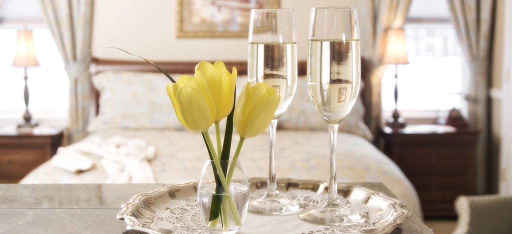 Vase with yellow tulips, champagne in crystal flutes on top of silver tray. Background faded picture of king sleigh bed with pale blue bedding with 2 windows.