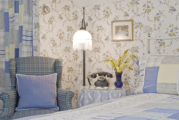 blue & green plaid wing chair with blue pillow, antique lamp, table with telephone & vase of flowers, king bed with blue plaid quilt