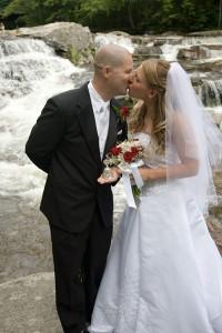 bride & groom kissing at waterfall