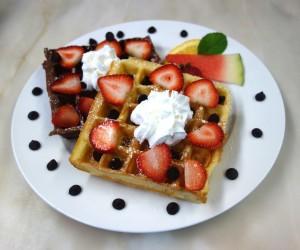 Chocolate & vanilla waffles with strawberries & whipped cream, chocolate chips around edge of white plate